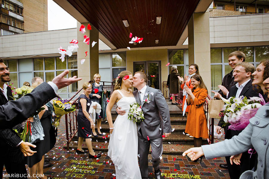 the bride and groom are excited and kiss after the wedding ceremony and guests on the street throw roses at them