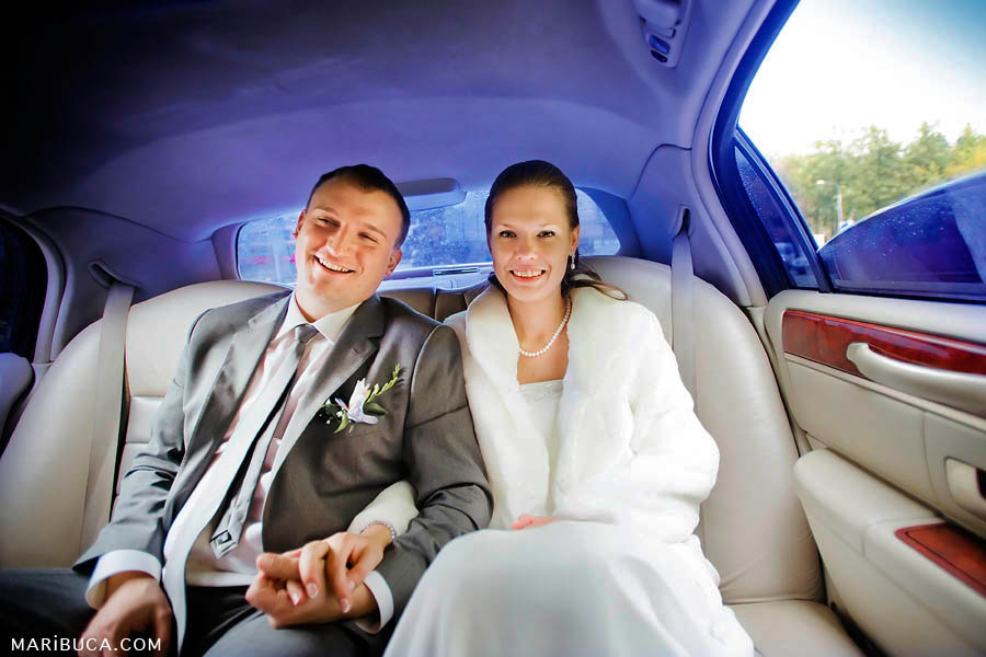 bride and groom are holding hands in the limousine with purple ceiling