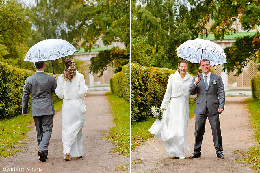 the bride in a white wedding dress and white fur jacket, the groom in a gray suit walk under an umbrella in the park.