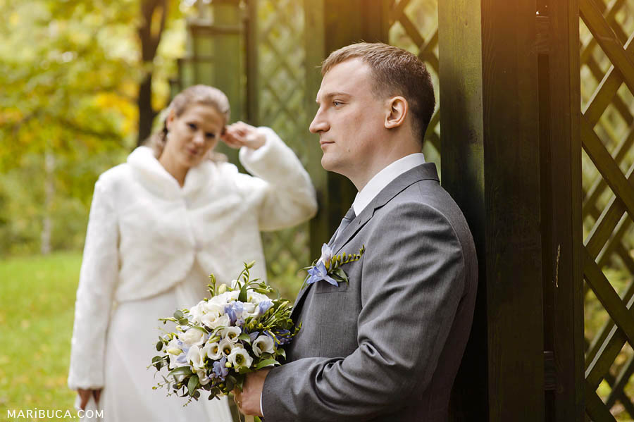 the groom is standing in profile and looking into the distance, the bride is standing behind and looking at him.