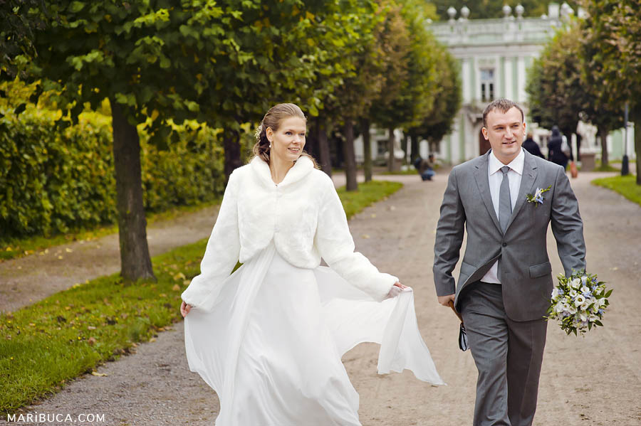 Bride and groom are walking in the beautiful park in the summertime