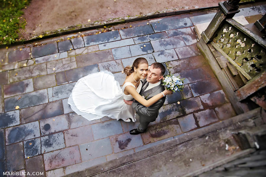 newlyweds stand and look up among the colorful, textured tiles around them.
