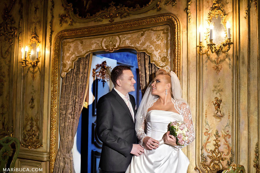 The groom and bride hold and look each other in front of golden beautiful wall with candelabra
