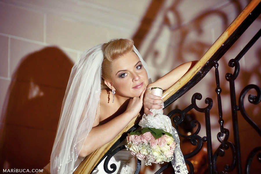 bride in veil with pink wedding bouquet leaned on railing stairs