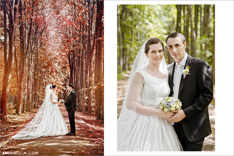 the bridegroom in a black suit and white tie, the bride in a long luxurious dress and a long veil. Newlyweds, hold each other's hands and look at each other against the backdrop of the wonderful atmosphere around the red and green forest in autumn.