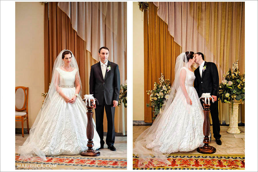 the bride and groom in the registry office kiss each other against the background of beige and brown curtains
