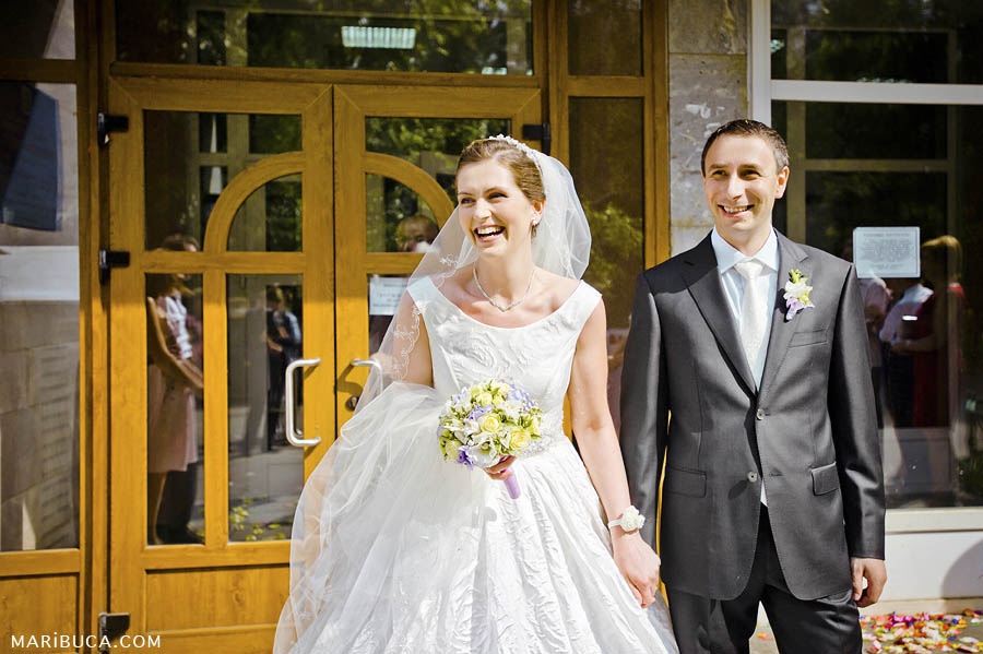 happy bride and groom leave the registry office