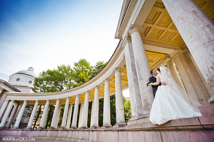 bride and groom stand and kiss each other in an architectural historical complex with white columns on a sunny day