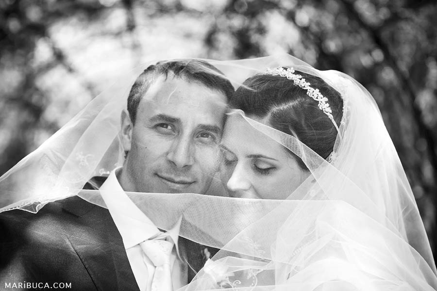 Black and white images as the a romantic moment where the groom and the bride are covered the wedding veil on them in the Ruby Hill, Pleasanton.