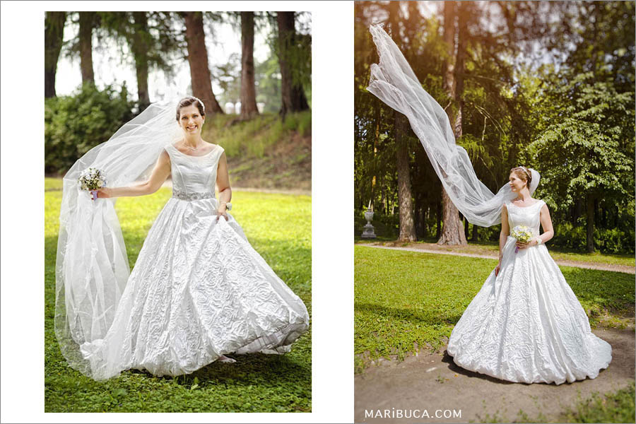 THe bride in white wedding dress tosses her long veil up on a background of trees in the park