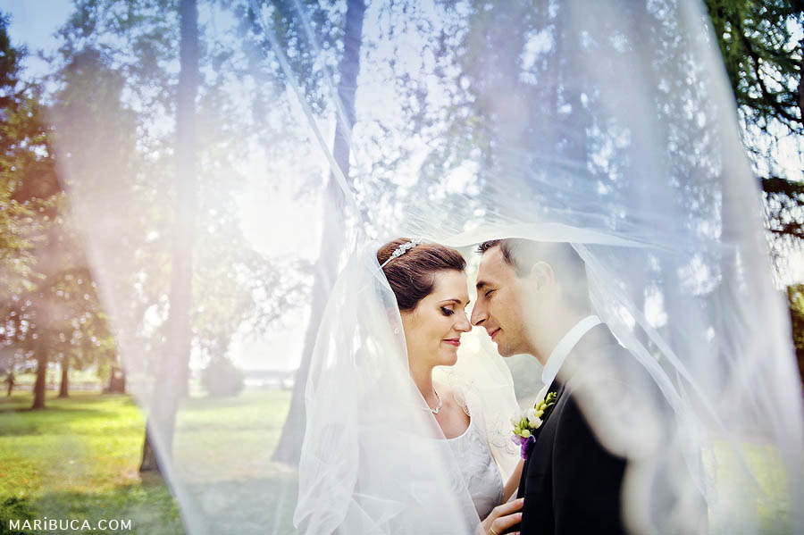 the newlyweds stand huddled together against the background of a developing veil in the garden.