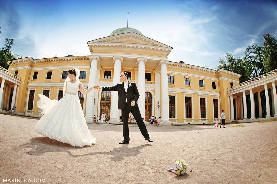 the bride and groom rehearse the first dance of the newlyweds on the background of a light yellow historic building.