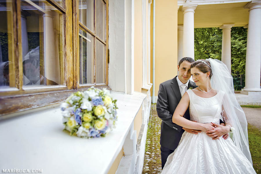 The pensive look of the bride and groom against the background of the yellow building and the bride's wedding bouquet.