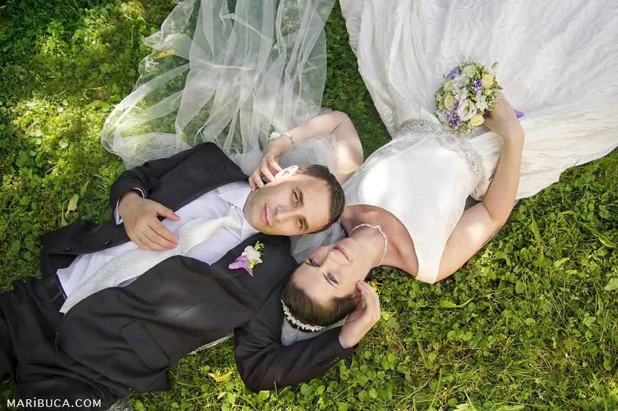 the bride and groom lie on their backs on the green grass and enjoy each other's company