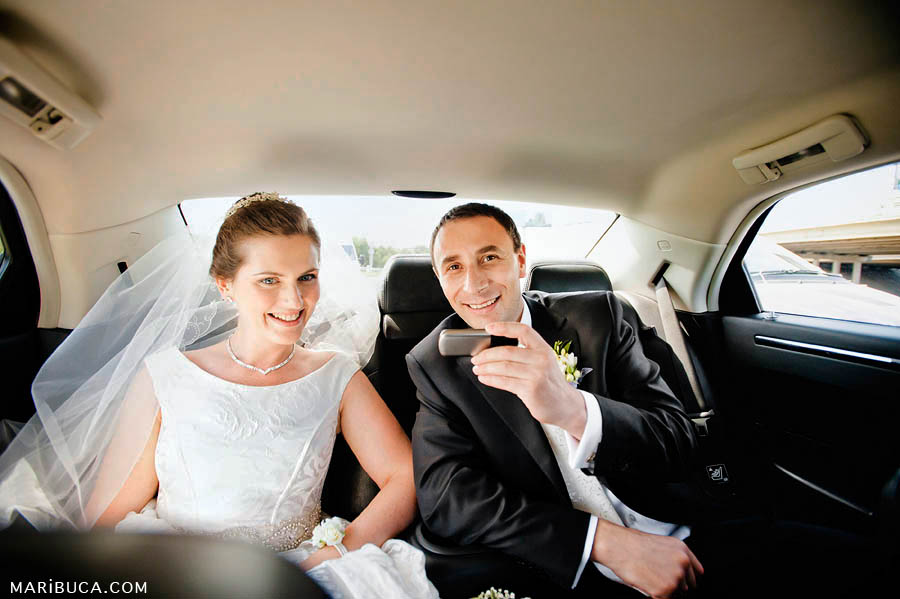 the bride and groom are sitting in the car and receive congratulations from friends and relatives.