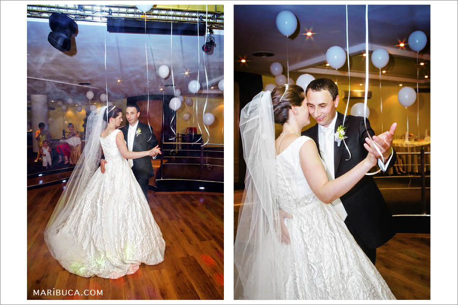 the first dance of the newlyweds in a restaurant surrounded by smog and white balls on the ceiling