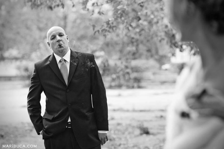 Self-confident groom smokes cigar in the park