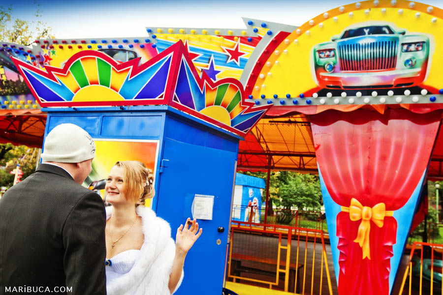 The bride and the groom look each other on the yellow-blue background in the amusement park