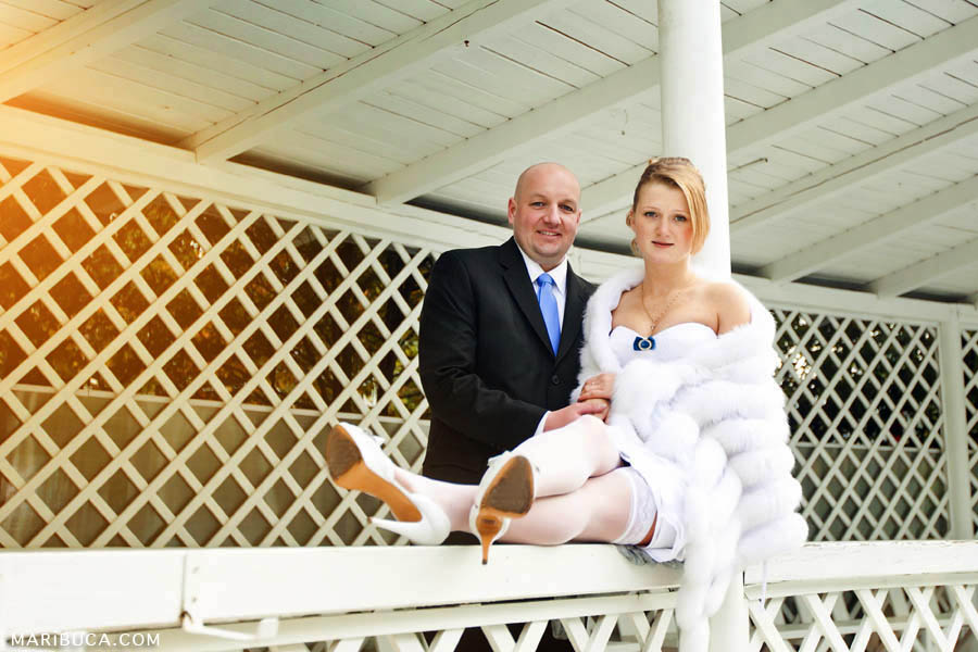 bride and groom sit on the railing in the park on a white background
