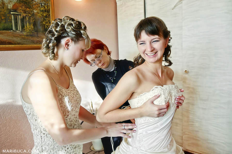 Bridesmaids help the bride during the getting ready