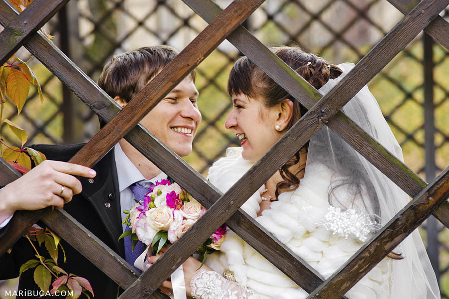 Bride and groom make faces through decorative brown fence