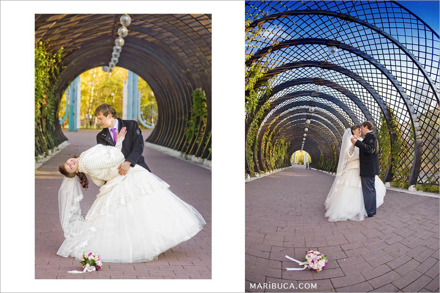 Bride and groom dancing the first dance in a decorative wooden semicircular arch