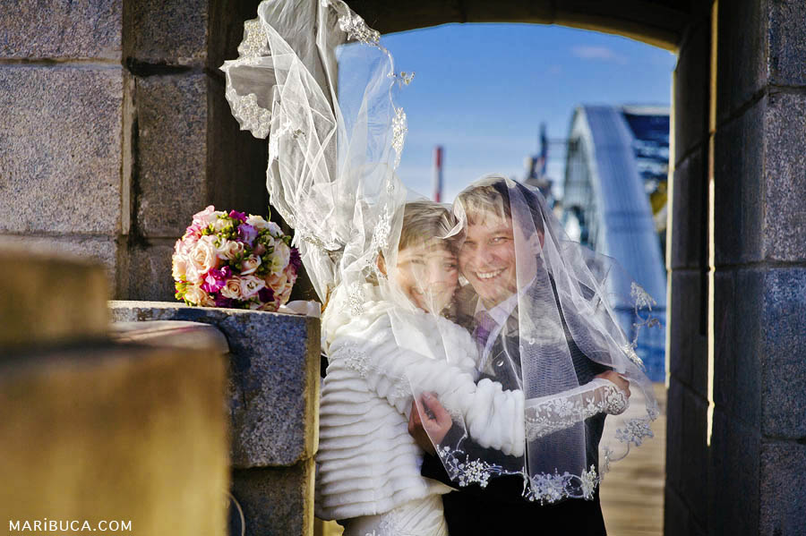 The bride and groom are covered with veils and part of the veil develops from the wind.