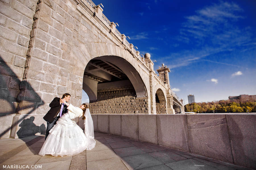 The bride and groom are dancing against the backdrop of a huge bridge and a deep blue sky.