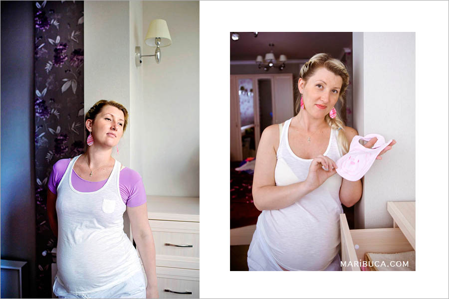 A pregnant girl stands near the wall in a white T-shirt and holds a pink apron for her newborn daughter.