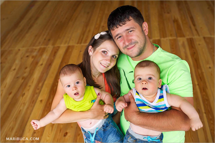 parents and their wonderful eight month old boys twins on a brown hard floor background in the San Ramon, Children Photographer Bay Area