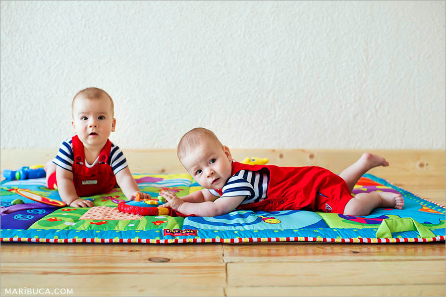 eight-month-old boys twins lie on a soft colored rug against a white wall