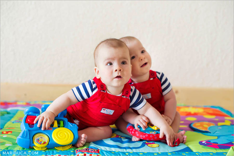 eight-month-old boys twins in red jumpsuits sit each other surrounded by toys, colored soft rug and white wall