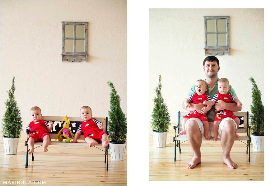 eight-month-old boys, twins in red jumpsuits, sit on a bench and on each side are green decorative Christmas trees. Dad with twins sitting on a bench.