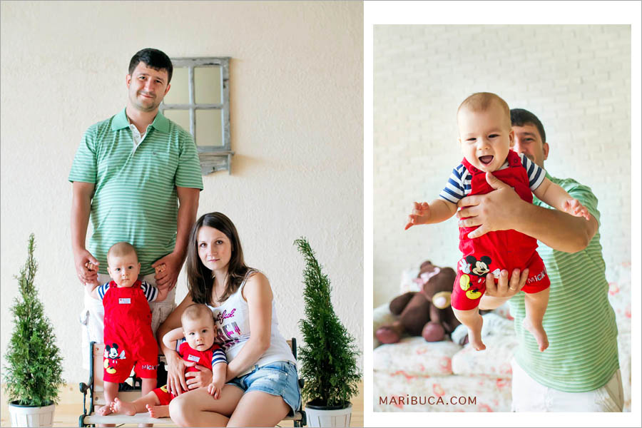 Mom, Dad and 8 month old sons are sitting around two Christmas trees and a beige background.
