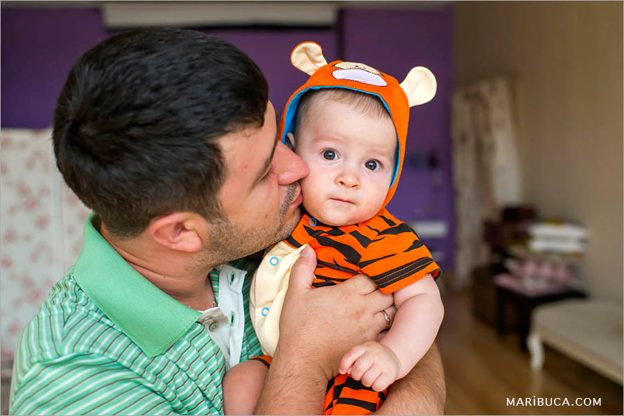 dad kisses an 8 month old son on the cheek, the baby is wearing a tiger cub's clothes on a beige background.