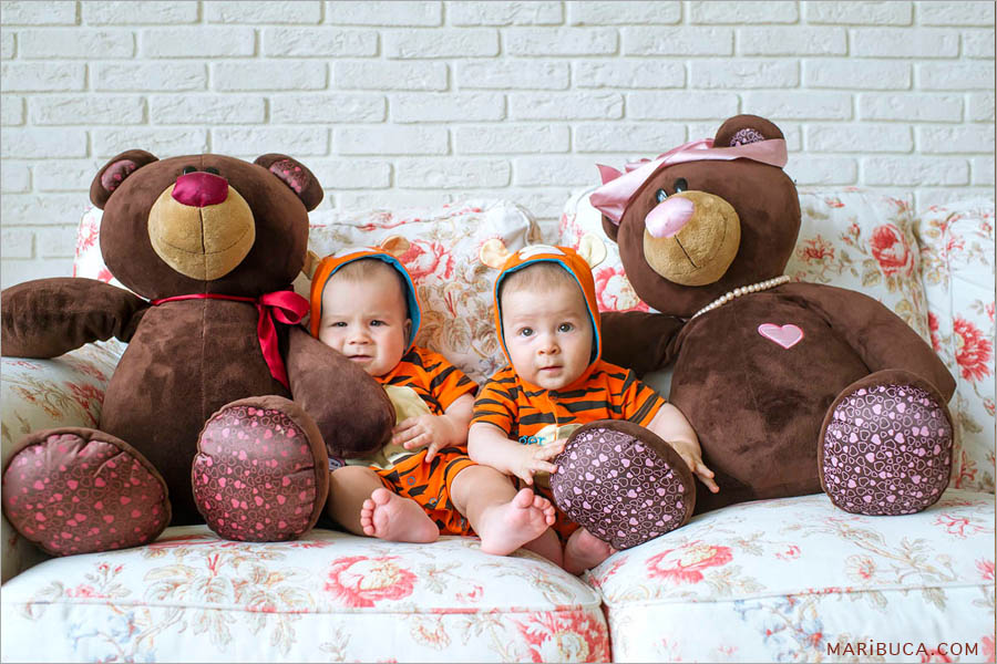 eight month old twin boys dressed in orange tiger clothes, sitting on the sofa and big brown soft bears toys on each side of them.