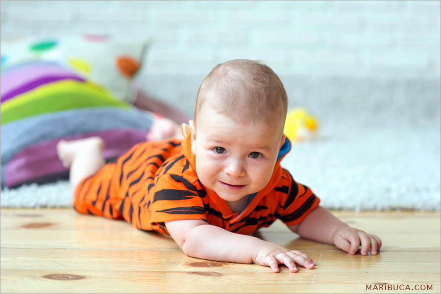 The portrait of an 8 month old baby in black and orange clothes lying on the floor.