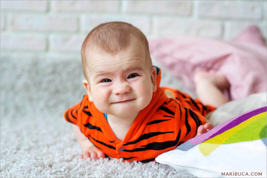 portrait of 8 month old baby in black and orange clothes has a serious look lies on the white carpet.