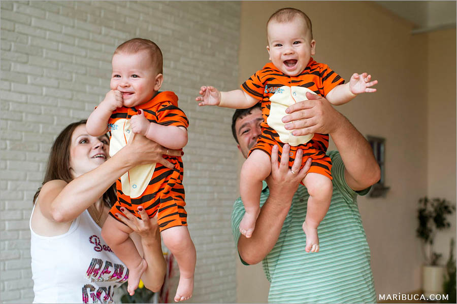 mom and dad are holding 8 month old twins in red jumpsuits on a beige background