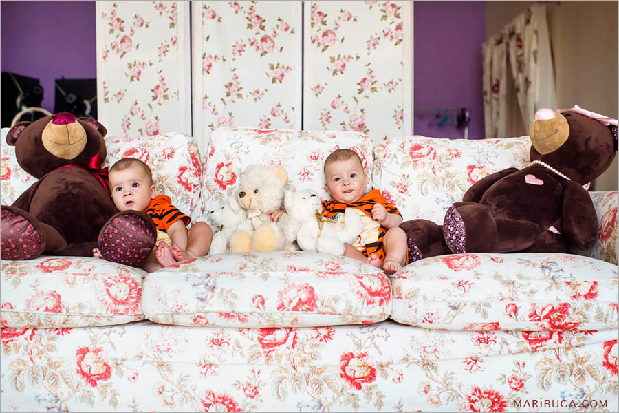 eight month old boys sit on a big white-red sofa surrounded by bears of different sizes.