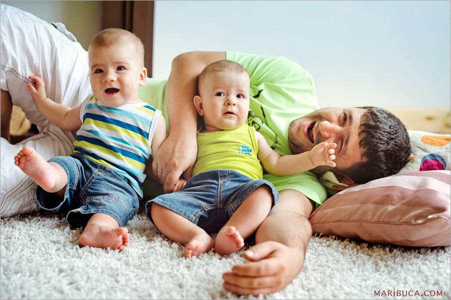 dad lies surrounded by two 8 month old twins in blue jeans