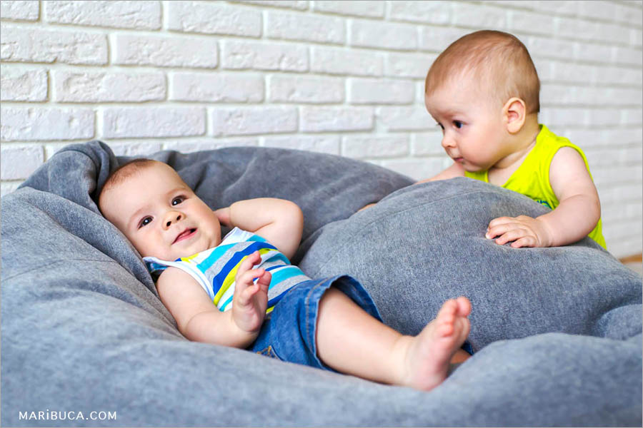 baby twins boys one of them stands and watches his brother lying on a gray sofa.