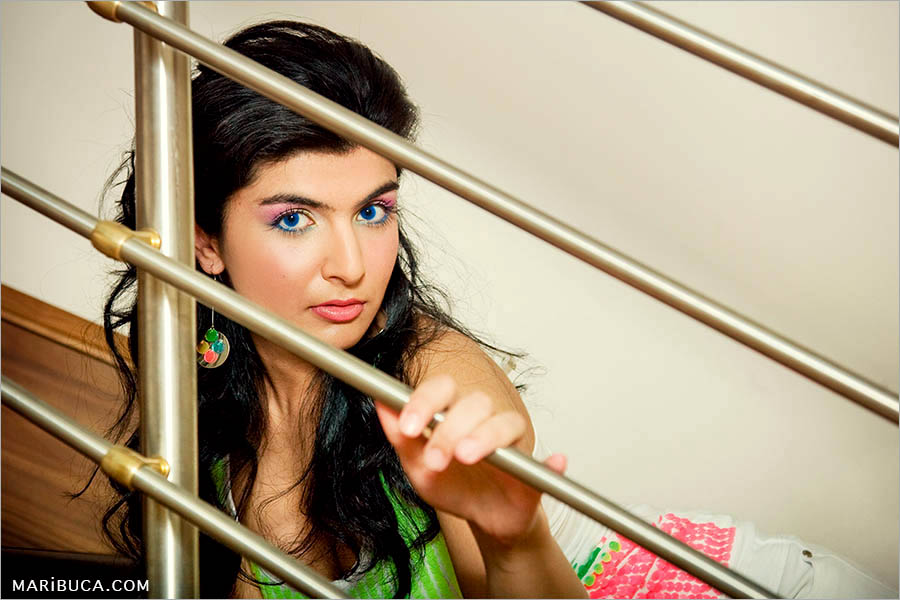 girl with long hair and green sweater is sitting on the stairs holding a railing