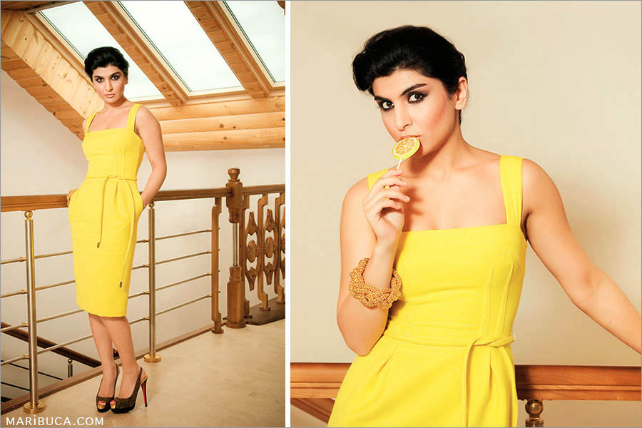 a girl with a yellow lollipop in her hands and a yellow bright yellow dress against the background of the windows of the house.