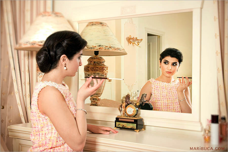 A modern girl in a light pink dress is looking at herself in a mirror holding a filter cigarette in her hand.