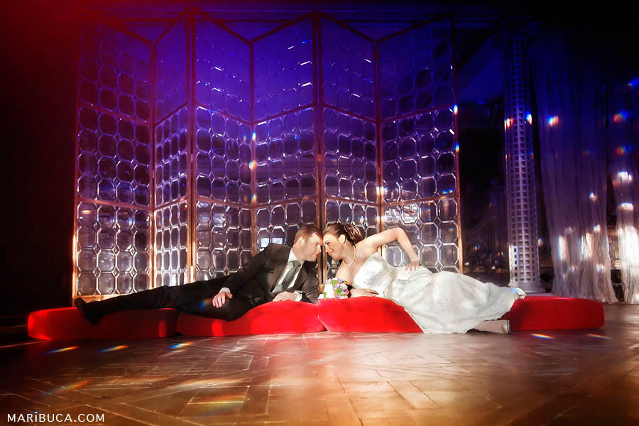 The bride and groom are lying on a red soft mattress around a glass screen in purple shades in the San Francisco