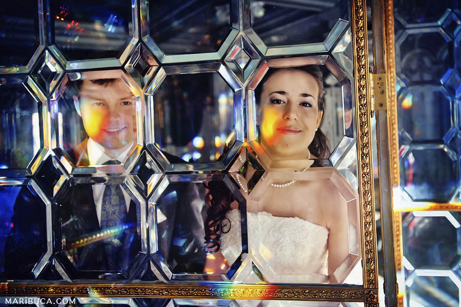 The bride and groom are smiling and looking through a textured glass screen with orange backlighting.