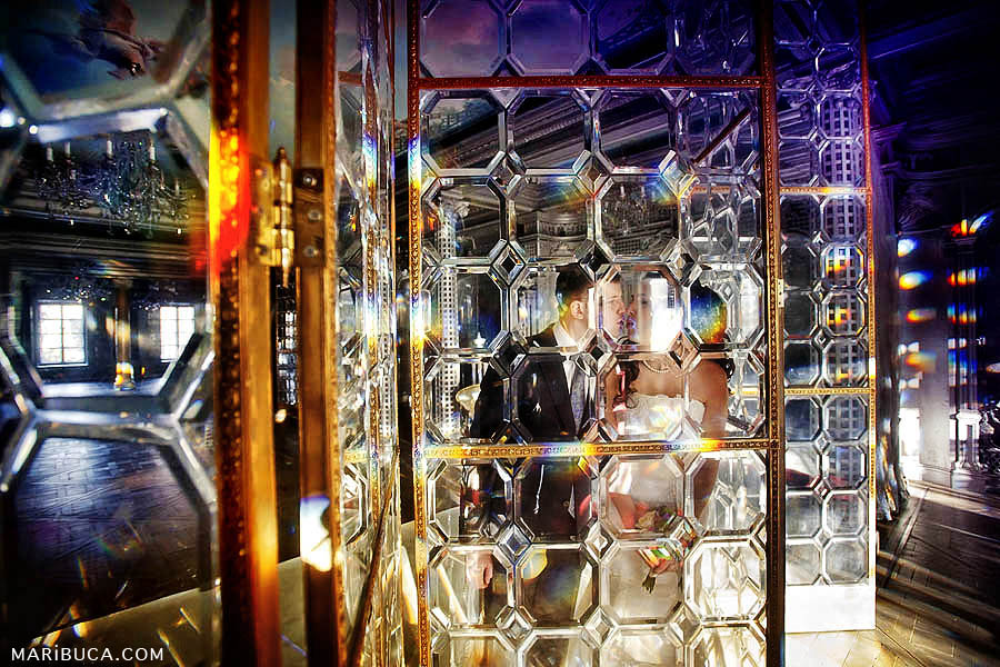 The bride and groom kiss each other through a textured glass screen with orange backlight.