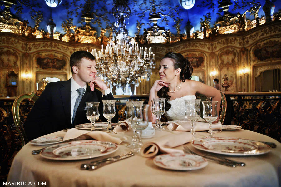 the bride and groom enjoy each other while sitting at the holiday table, and on the background of a massive crystal chandelier in brown tones walls.