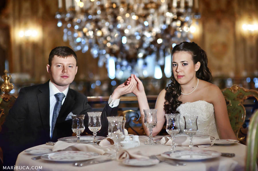 newlyweds with a serious look hold hands and sit at the table in the brown tones of the background.